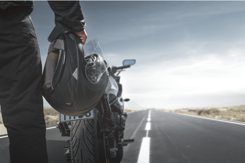 Man holding a helmet next to a motorcycle on the open road