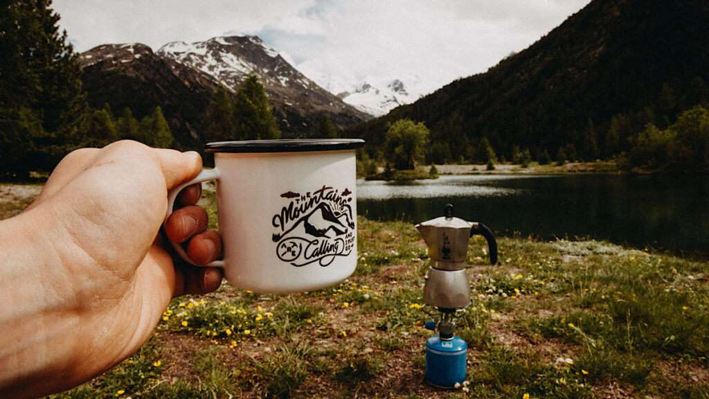 Hand holding a cup in front of a moka pot on s camping stove in front of mountains