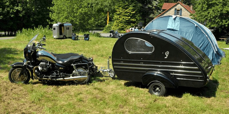 Black teardrop camper connected to a motorcycle