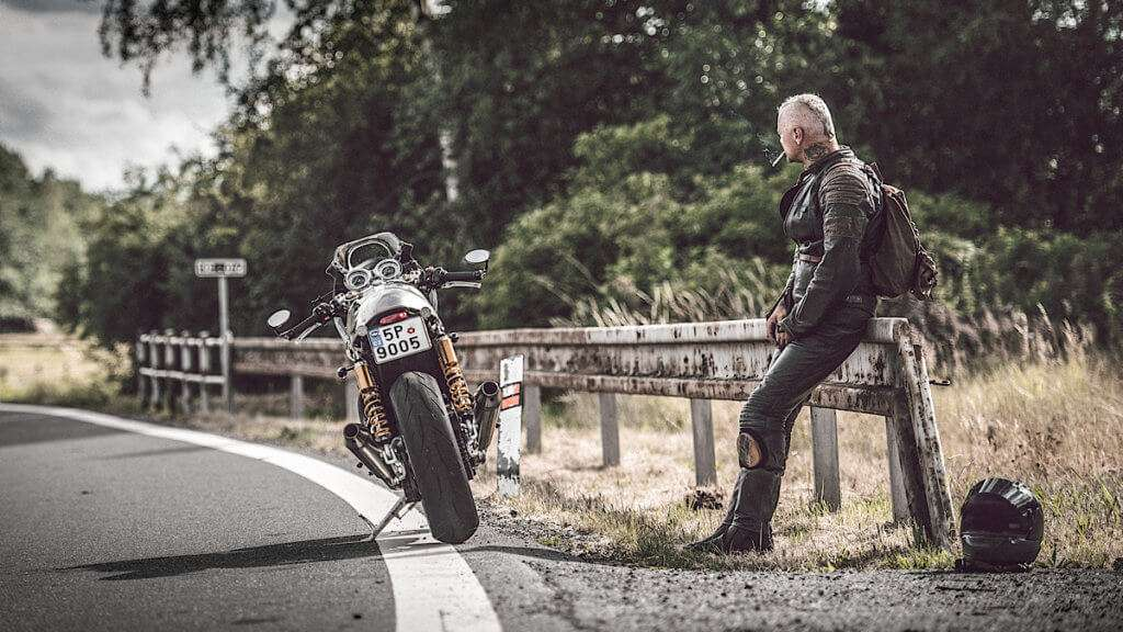 Man on the side of the road next to a motorcycle
