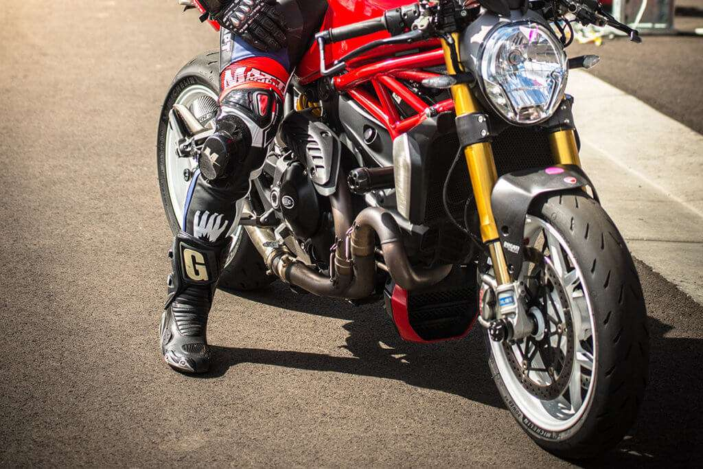 Person wearing racing shoes on a red motorcycle