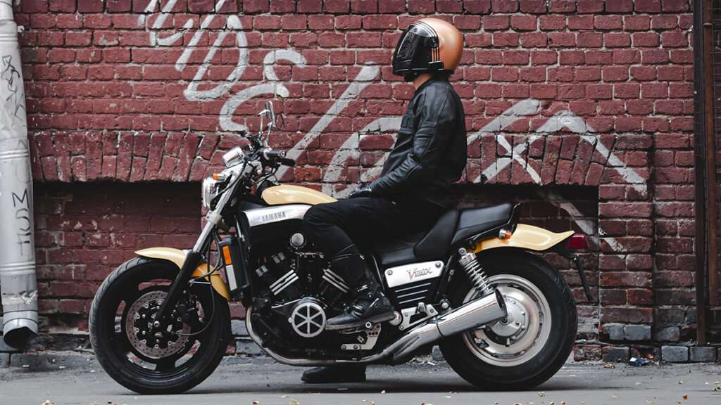Person wearing motorcycle black boots on a yellow motorcycle