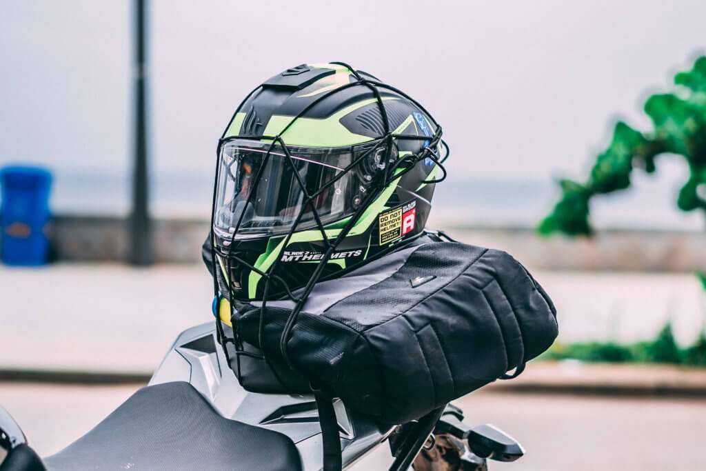 Motorcycle helmet strapped to the back of the motorcycle