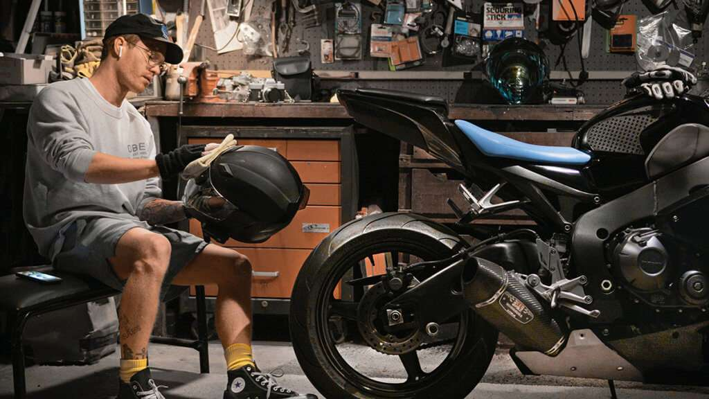 Man cleaning this motorcycle helmet in a garage next to a motorcycle