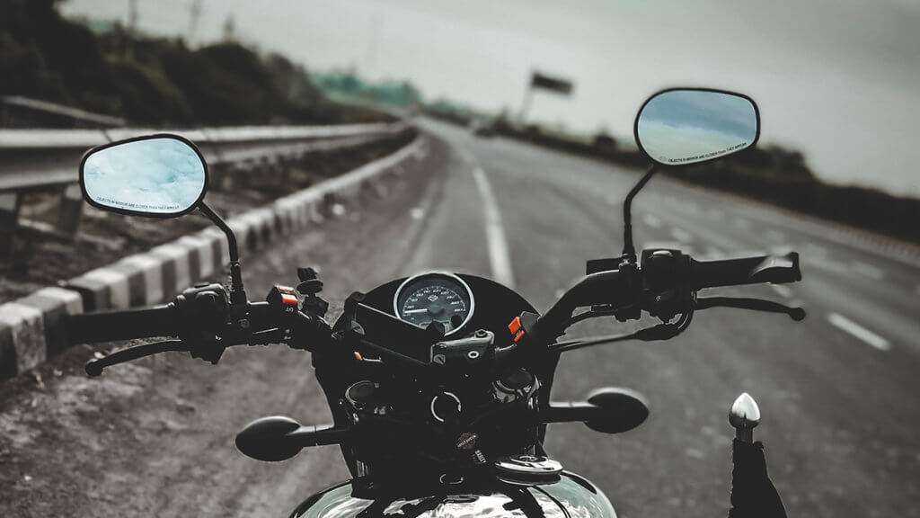 Close-up of motorcycle dashboard with mirrors stopped on the side of the road