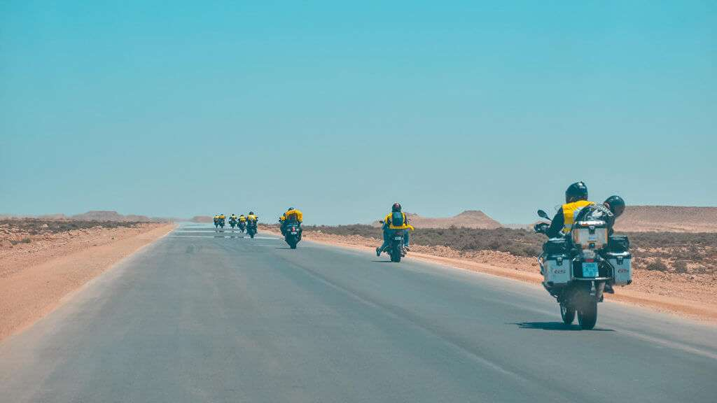 Group of motorcycle riders spread out on a desert highway