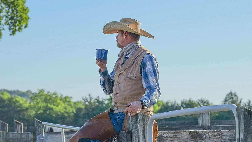 Cowboy wearing chaps and drinking from a cup