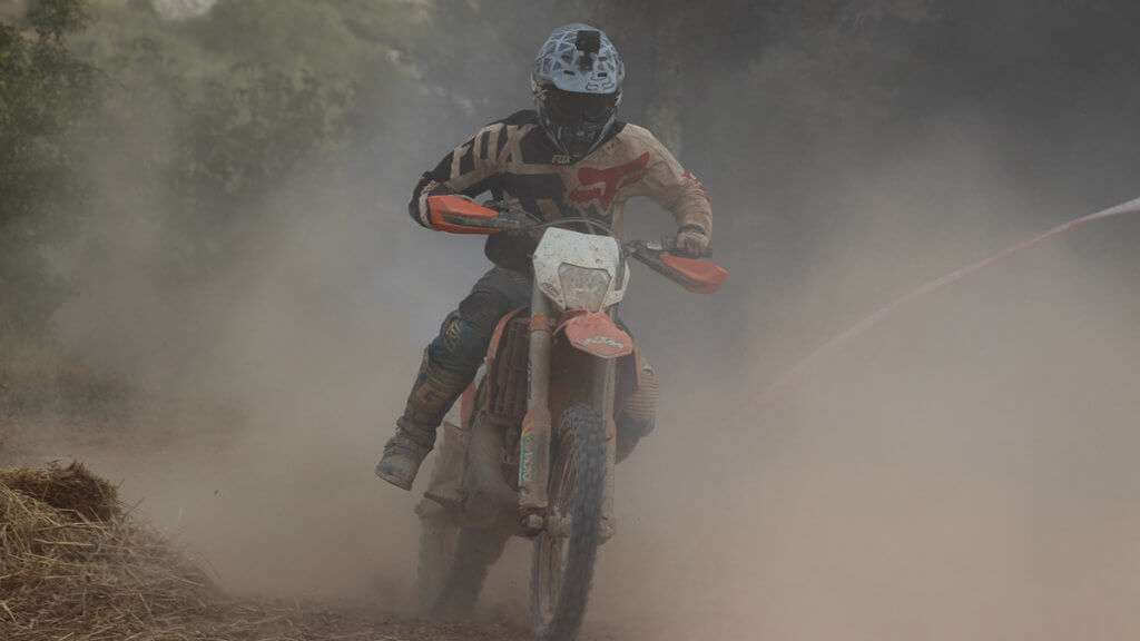 Person riding motocross dirtbike in a dust cloud