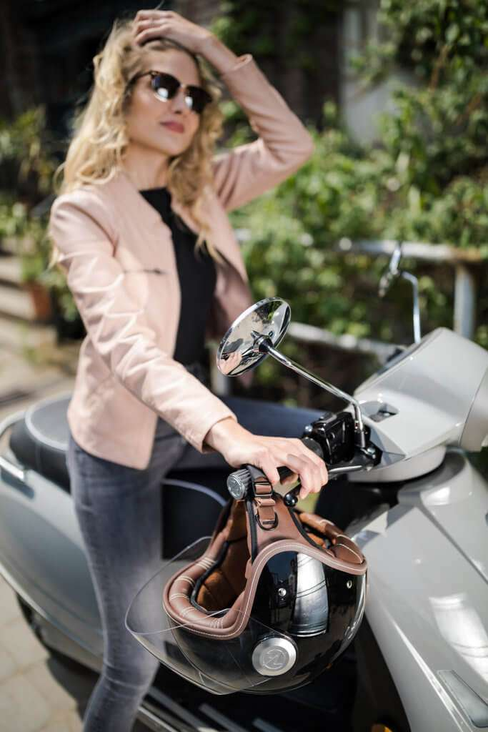 Woman in beige coat on a scooter with an open face helmet on the handlebar