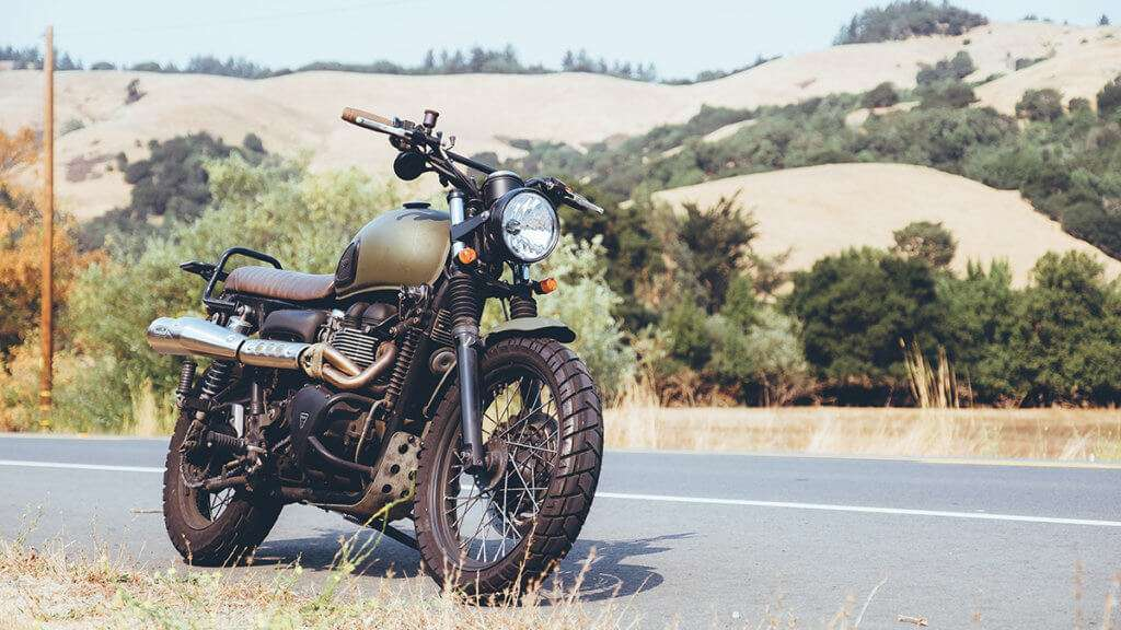 Dark green motorcycle on the side of the road