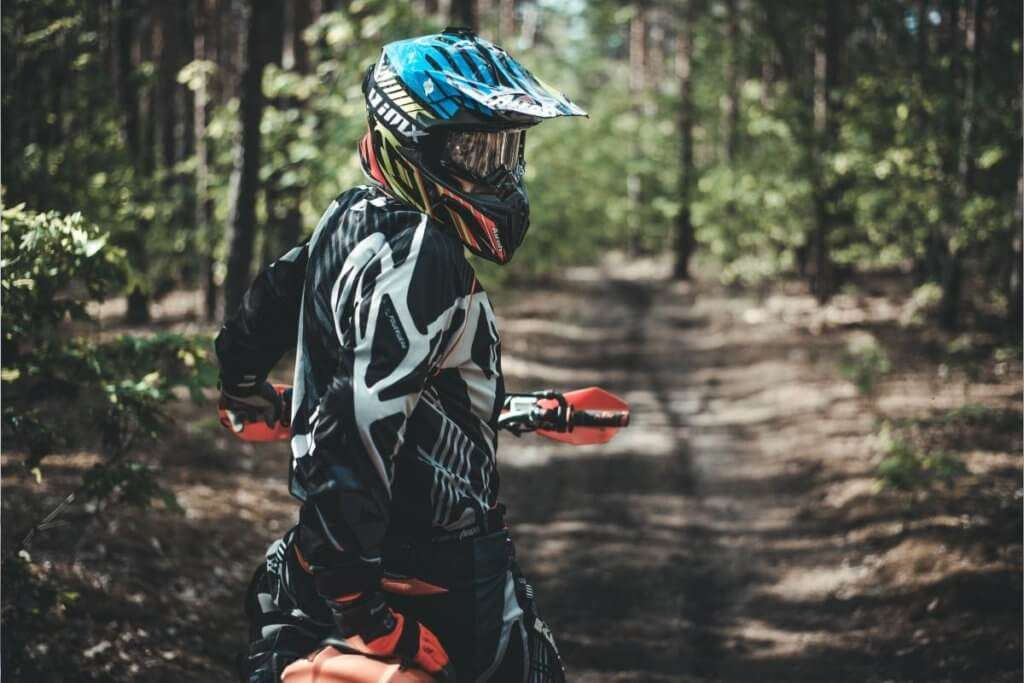 person wearing a motocross helmet and suit looking back