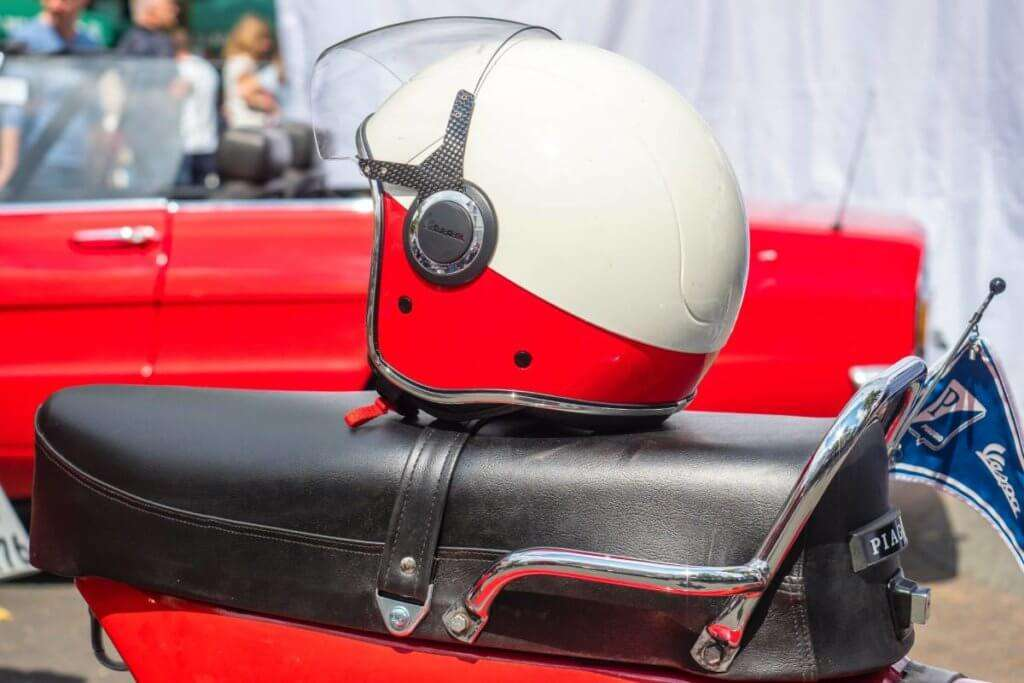 white and red helmet on top of a motorcycle seat