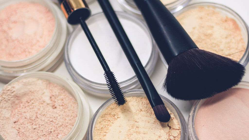 Three makeup brushes on top of powder