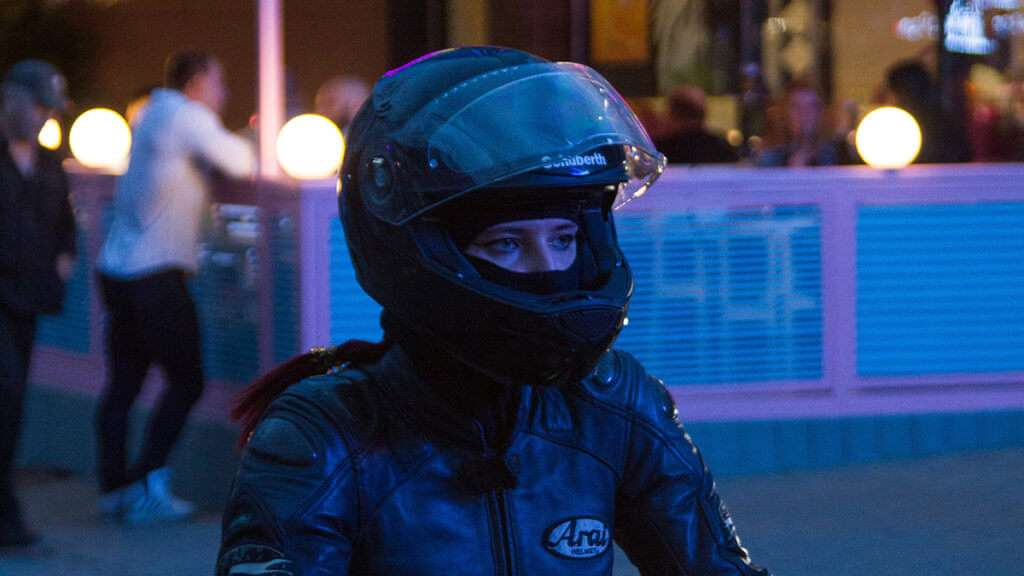 Woman with full-face helmet and a black jacket