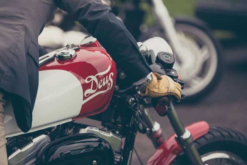 Person riding red and white motorcycle wearing light leather gloves
