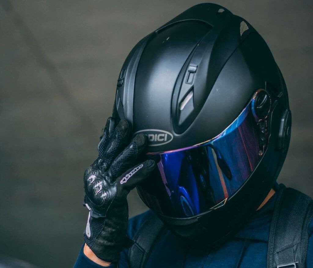Person with black motorcycle helmet holding hand on the visor