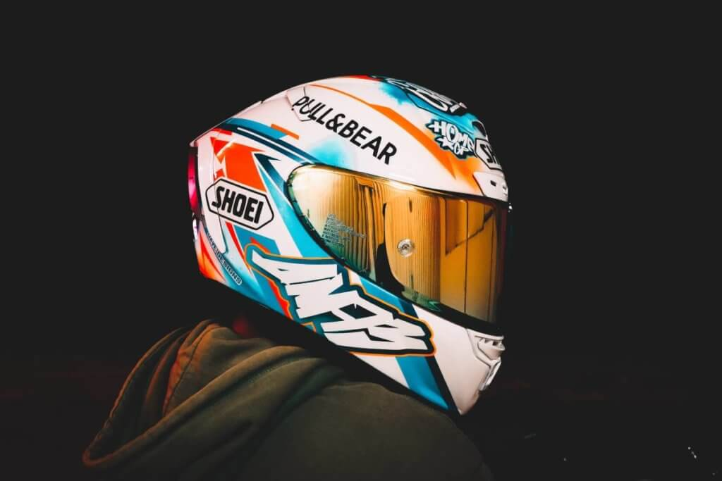 Person wearing a white Shoei Motorcycle helmet with graffiti-style decals