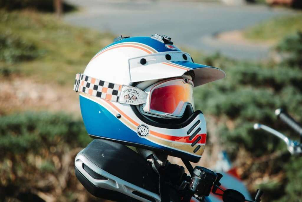 White blue and red motorcycle helmet with glasses on top