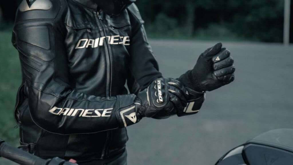 Man in black leather motorcycle jacket putting on black Dainese gloves