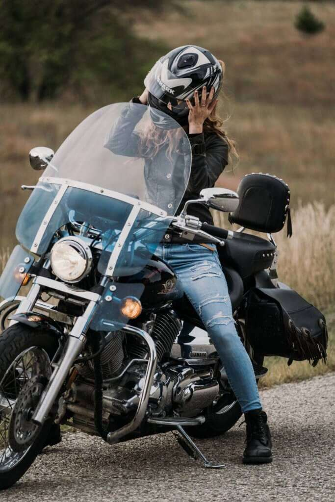 Woman taking off her helmet on a black motorcycle with a windshield