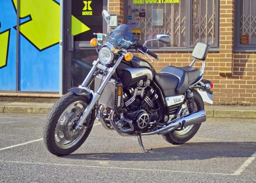 Black and grey motorcycle parked in front of a brick building