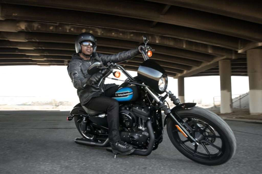 Man riding a motorcycle wearing a gray leather jacket