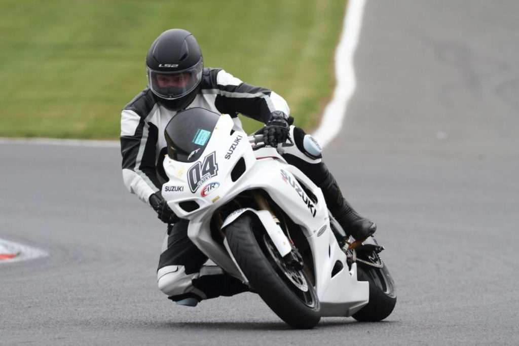 White racing motorcycle with rider wearing full body equipment