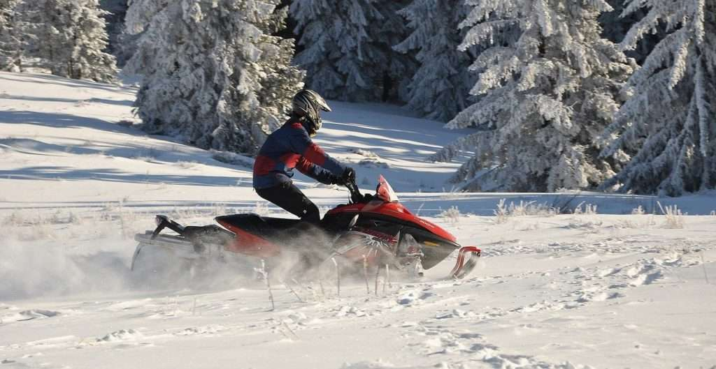 Person riding a red snowmobile