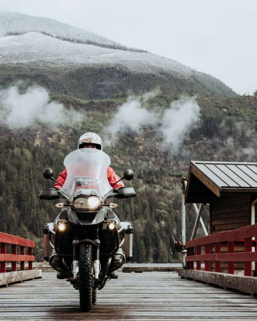 Person riding an adventure motorcycle on a wet bridge with clouds above