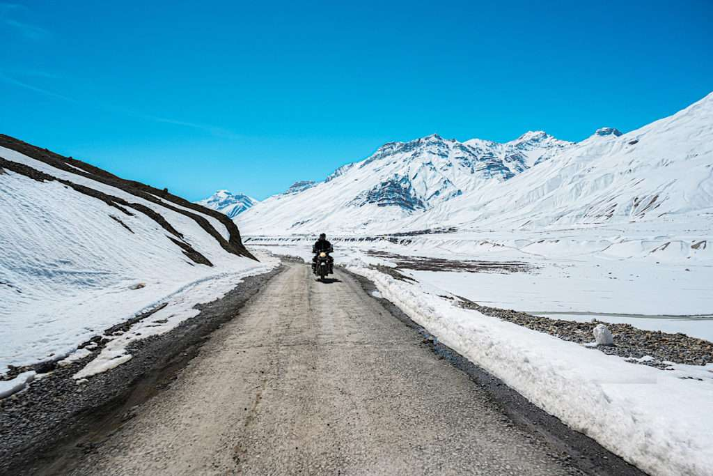 Motorcycle on a mountain road with snow covered mountains in the background