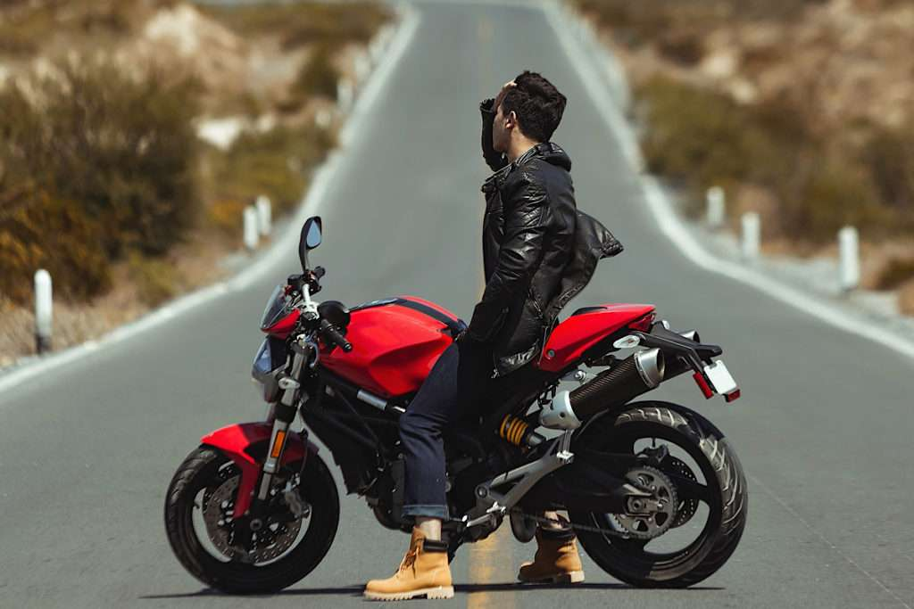 Man on red motorcycle wearing a black jacket