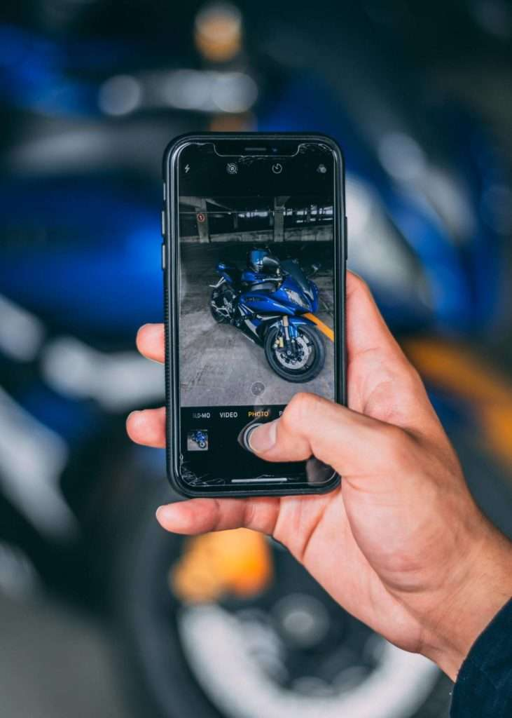 Person taking a photo of a motorcycle