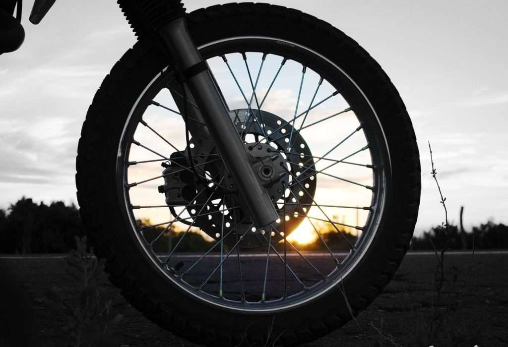 Motorcycle front wheel at sunset