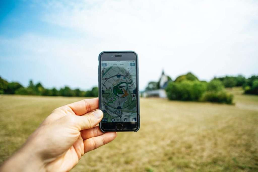 Hand holding a phone with a GPS map on it