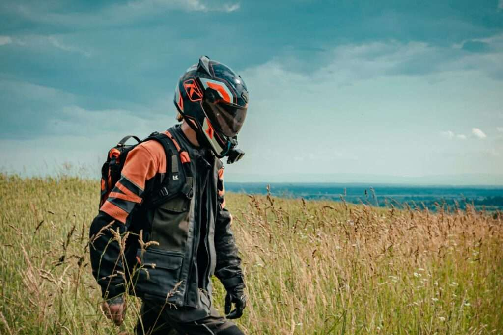 Man with motorcycle jacket and helmet on walking in a field
